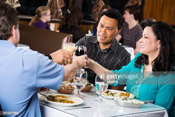 Double date at a restaurant raising glasses in toast