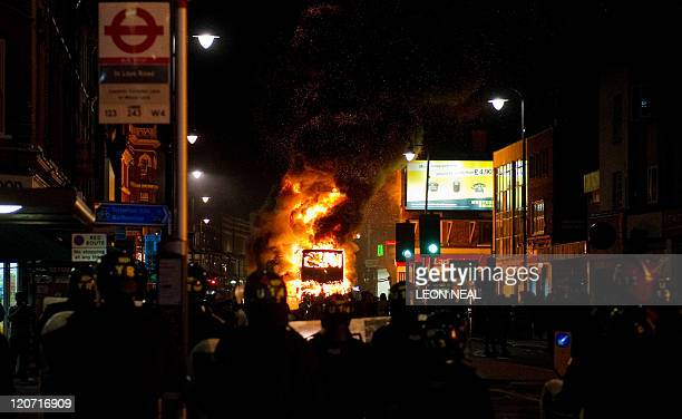 Double decker bus burns as riot police try to contain a large group of people on a main road in Tottenham, north London on August 6 2011. Two police...