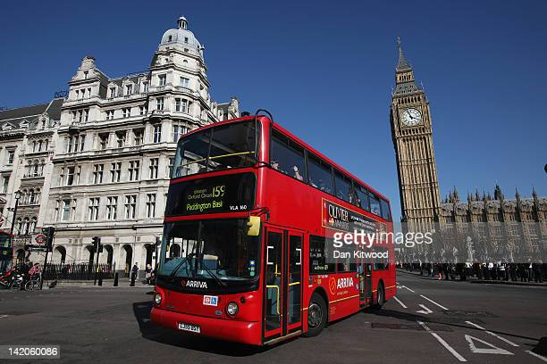A double decker bus makes its way past the Houses of Parliament on March 27 2012 in London England