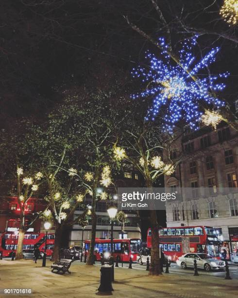 Double decker buses drive around Sloane Square with Christmas decoration in Chelsea, London, England