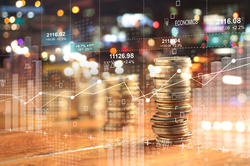 Double explosure with businesss charts of graph and rows of coins for finance at night city background. 1051617040