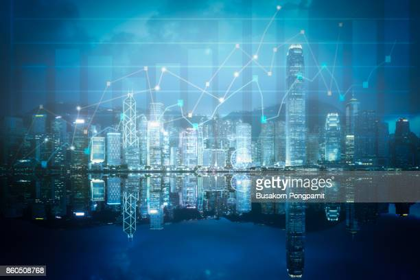 Double exposure business technology at abstract financial charts in sky on city background. Business information concept