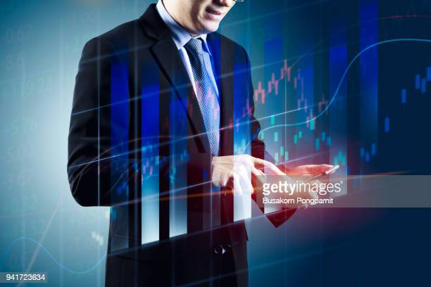 Double exposure businessman hand holding smart phone and stock market for financial investment concept.