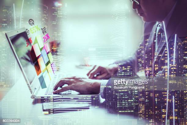 Double exposure businessman hand working on laptop with chart finance and technology