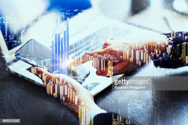 Double exposure businessman hand working on smartphone with chart finance and technology
