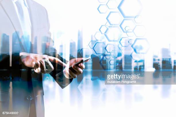 Double exposure businessman with  using on smartphone  digital modern city, concepts of technology business development