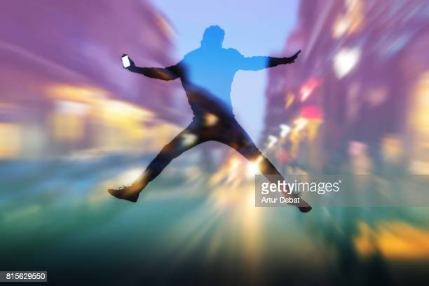 Double exposure effect of the silhouette of guy jumping with bright screen smart phone on hand with a city at night with motion and lights.
