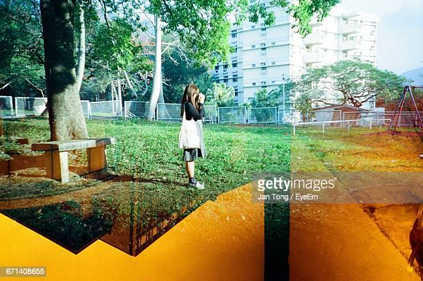 Double Exposure Image Of Woman Photographing In Park And Orange Sky
