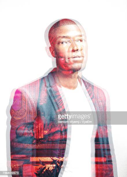 Double Exposure Image Of Young Man And Buddha Statue Against White Background