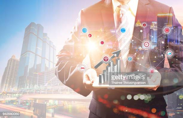 Double exposure of a businessman and a city using a smart hand holding phone futuristic connection technology, The concept of modern life, business, city life and internet of things.