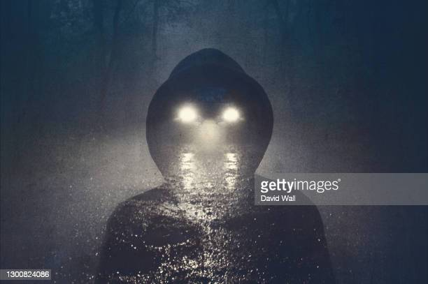 a double exposure of a ghostly blurred hooded figure. with car headlights as eyes. on a spooky country track. on a misty evening in the countryside. with a grunge, abstract edit. - mystery stock pictures, royalty-free photos & images