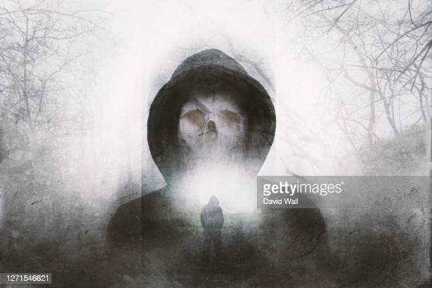 a double exposure of a scary hooded figure with a skull for a face. over layered with a forest in winter. with a blurred, grunge, abstract edit - winter stock pictures, royalty-free photos & images