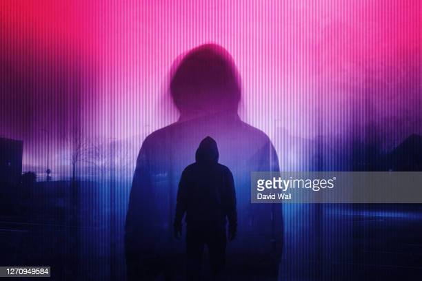 a double exposure of a silhouette of a mysterious hooded figure without a face. standing in a city at night. with a glitch, neon edit - crime stock pictures, royalty-free photos & images