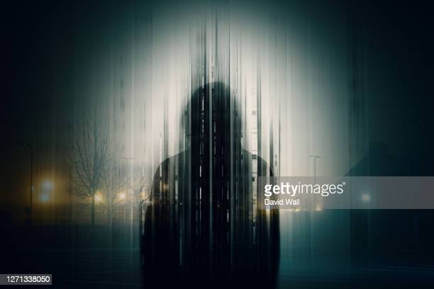 a double exposure of a silhouette of a mysterious hooded figure without a face, in a city at night. with a glitch, edit - crime stock pictures, royalty-free photos & images