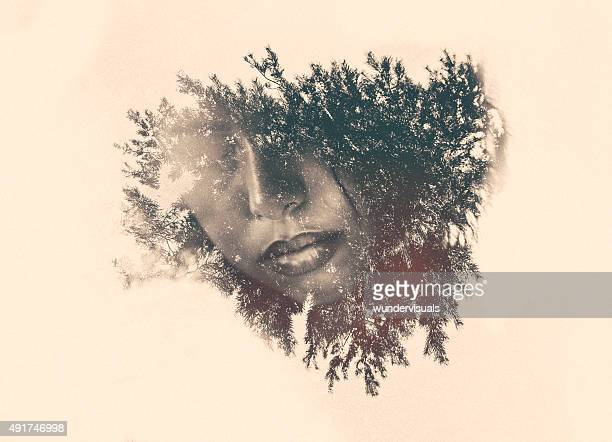 Double exposure of a woman's mouth within foliage