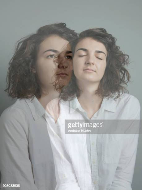 Double exposure of a young woman in her late teens wearing a white shirt with her eys closed and open in front of a gray background, portrait.