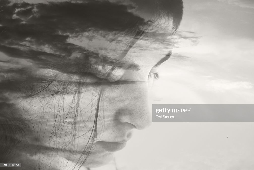 Double exposure of a young woman's face and clouds : Stock Photo