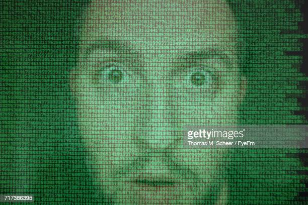 Double Exposure Of Binary Codes And Shocked Man Against Black Background