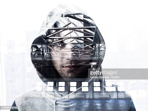 double exposure of bridge and man wearing hooded jacket - mehrfachbelichtung stock-fotos und bilder