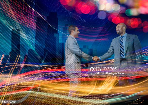 Double exposure of business people shaking hands in light stream