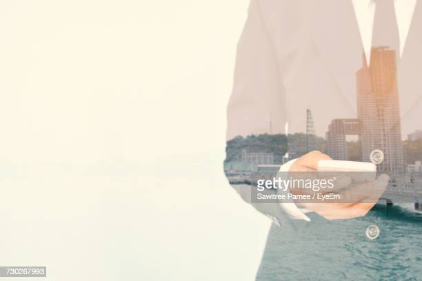 Double Exposure Of Business Person Against Cityscape