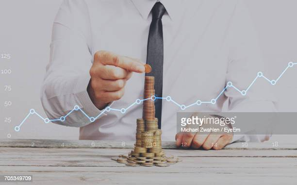 Double Exposure Of Businessman Arranging Coins And Line Graph