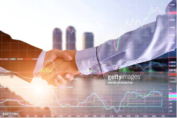 Double exposure of   Businessman groups Handshake for business and technical stock market bar chart on blurred city background. Finance concept.
