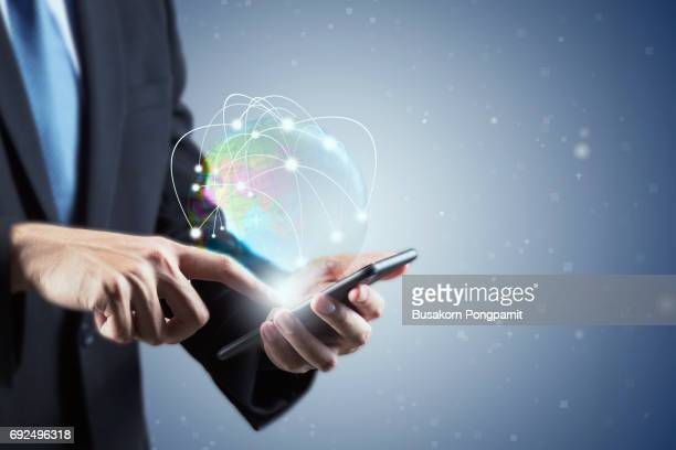 Double exposure of  Businessman hand using smartphone with world hologram in technology and social concept holding smartphone with digital graphic