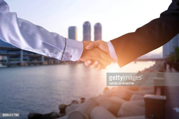 Double exposure of   Businessman  handshake for business and blurred city background.