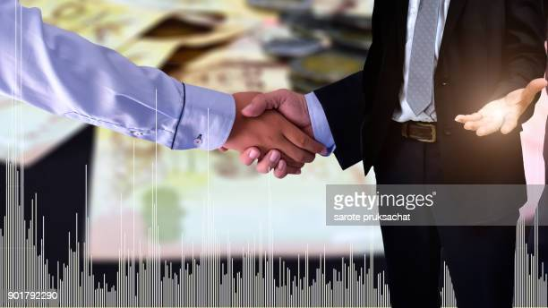 Double exposure of   Businessman Handshake for business and technical stock market bar chart on blurred money background. Finance concept.