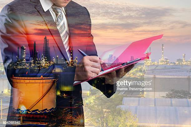 Double exposure of Businessman in a suit signing or writing a document