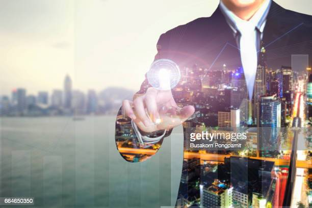 Double exposure of businessman press graph on blurred cityscape and financial building background, Business Trading concept