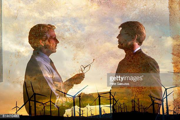 Double exposure of businessmen and wind turbines
