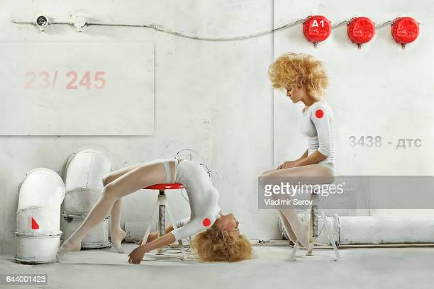 Double exposure of Caucasian dancer posing on stool