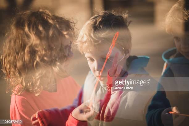 Double Exposure of Children Blowing Bubbles