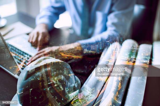 Double exposure of city and businessman working computer notebook as Business development concept.