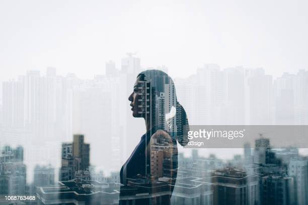 double exposure of confidence businesswoman over urban cityscape - prosperity stock pictures, royalty-free photos & images