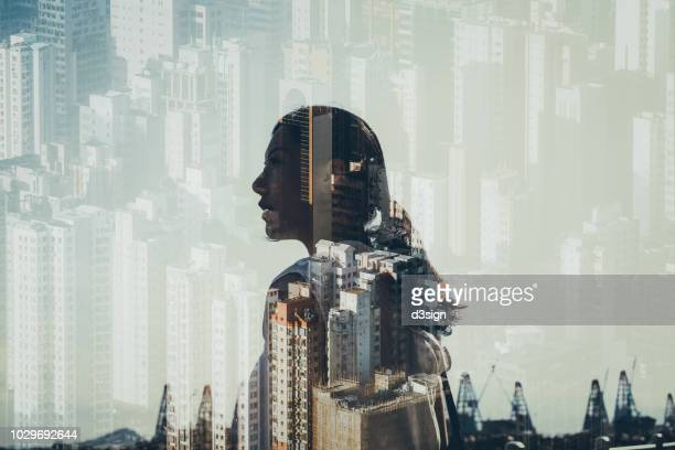 double exposure of confidence young woman over cityscape - mehrfachbelichtung stock-fotos und bilder