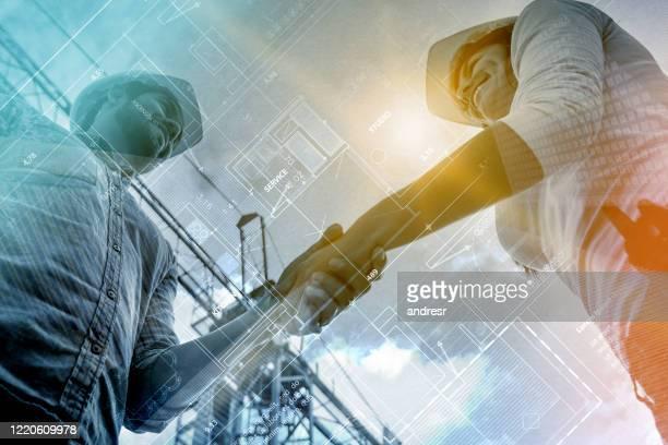 double exposure of contractors handshaking at a construction site - composizione digitale foto e immagini stock