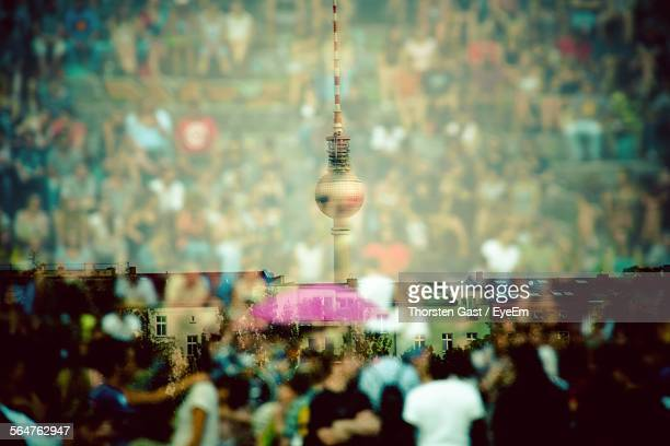 Double Exposure Of Crowd And Communications Tower