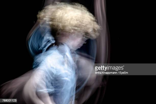 Double Exposure Of Dancing Man Against Black Background