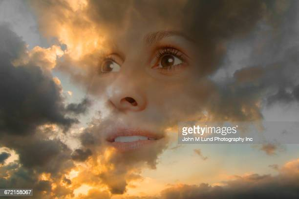 Double exposure of face of woman in sunset sky