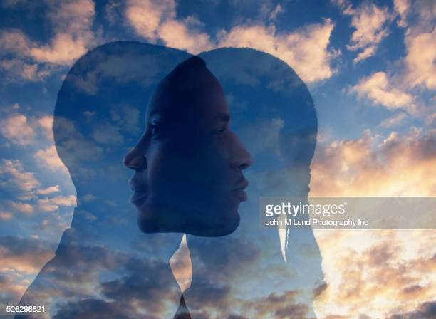 Double exposure of faces in dramatic sky