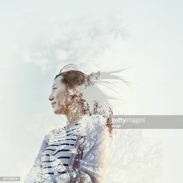 Double exposure of female and tree in nature
