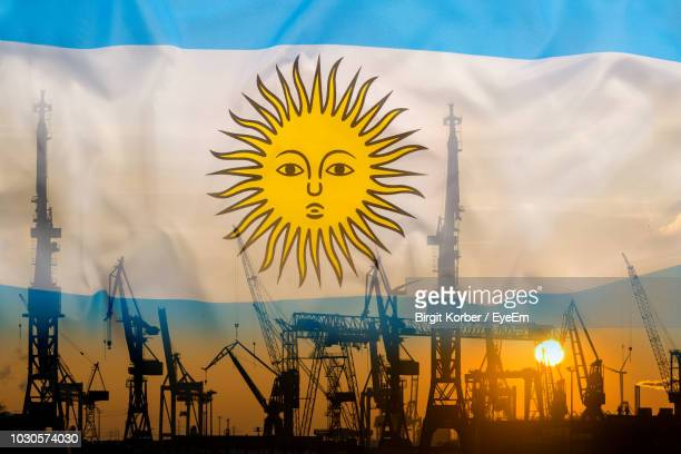 double exposure of flag and construction machinery during sunset - argentinas flagga bildbanksfoton och bilder