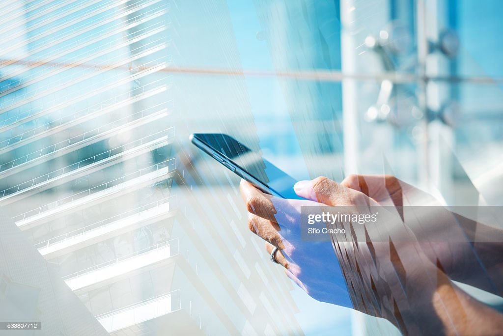 Double exposure of hands with smartphone and the city : Foto stock
