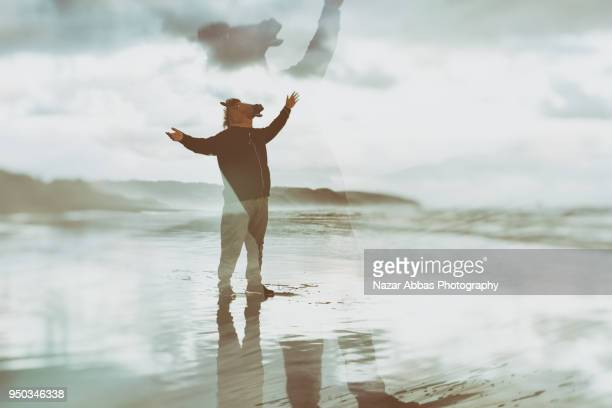 Double exposure of horse head man at beach.
