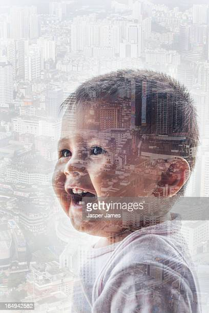 double exposure of laughing baby and cityscape