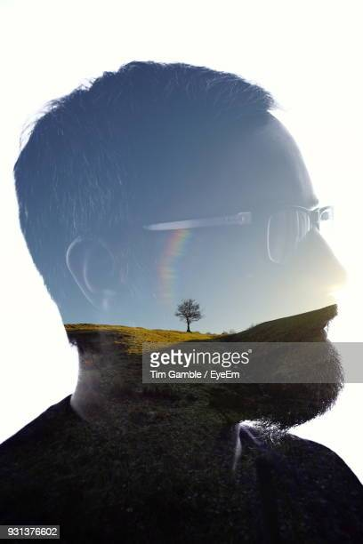 double exposure of man and field against sky - mehrfachbelichtung stock-fotos und bilder