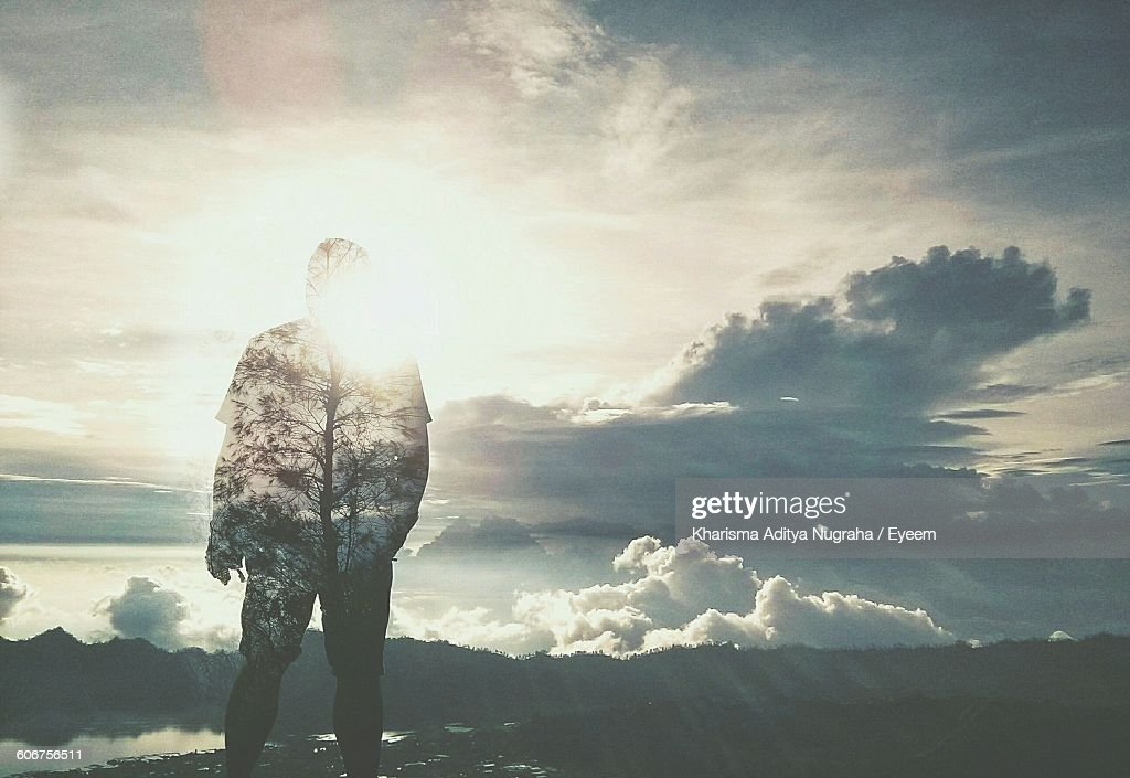 Double Exposure Of Man And Tree Against Cloudy Sky On Sunny Day : Stockfoto